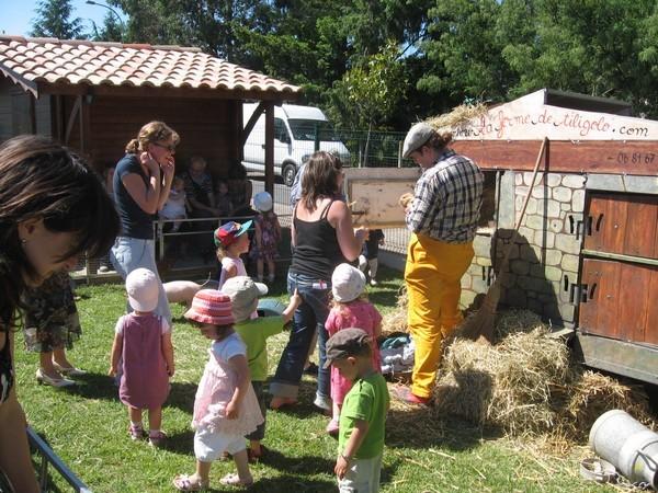 Les enfants entrent dans la ferme de Tiligolo et caressent les animaux
